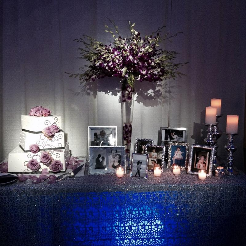 Cake Table Scape, purple dendrobiums, silver picture frames, pillar candles,